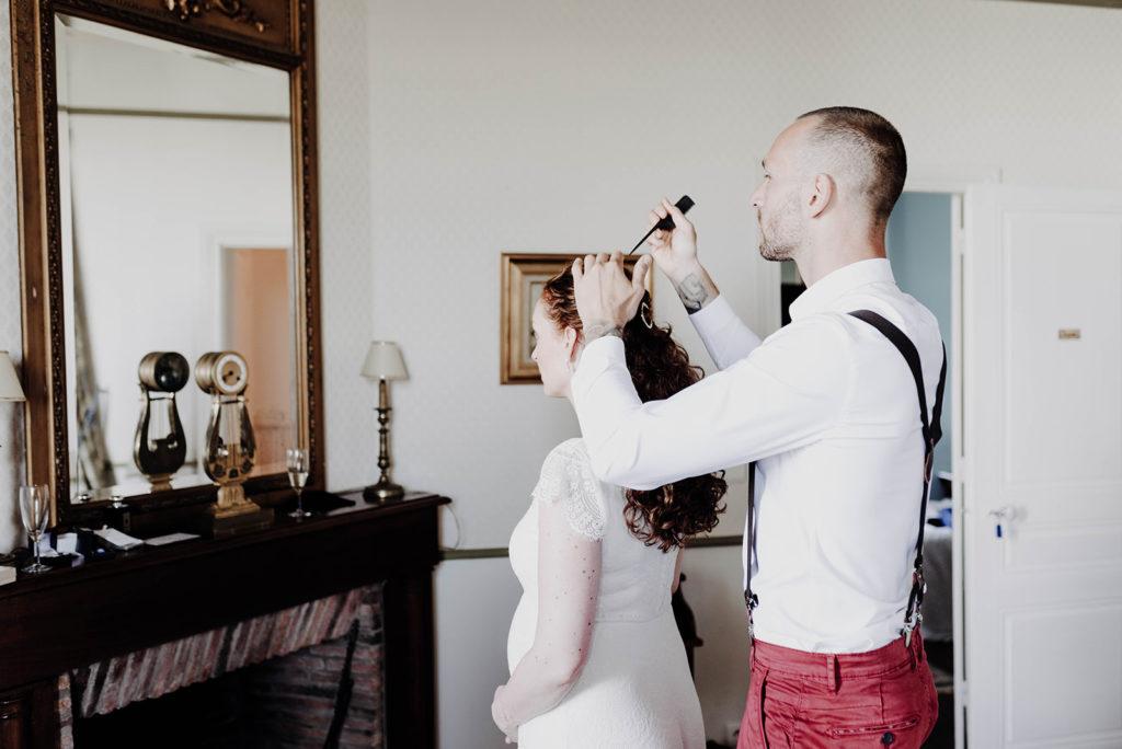 Coiffeur retouche cheveux mariée dans chambre de château
