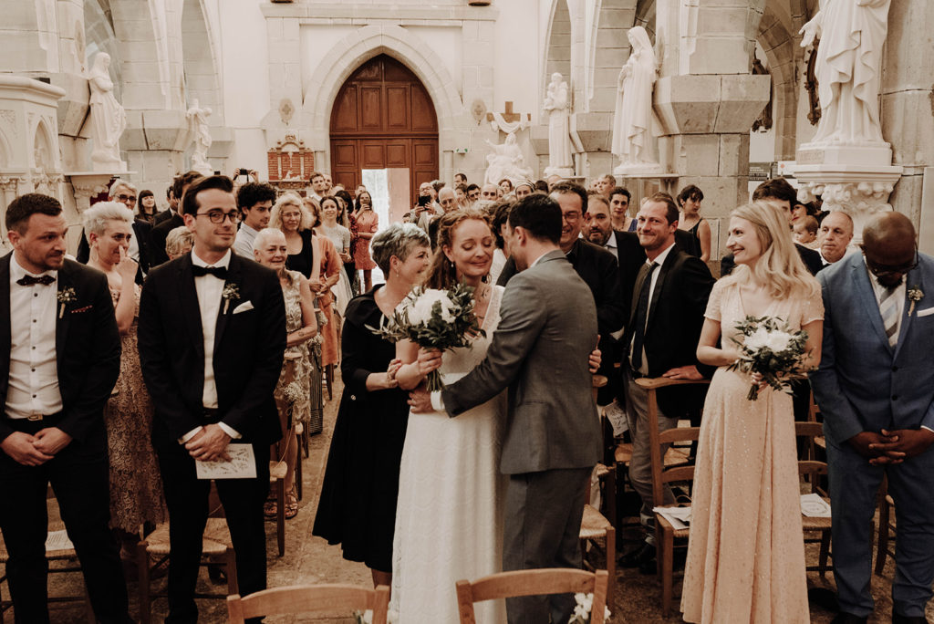 mariée émue embrasse son futur marié dans l'allée de l'église