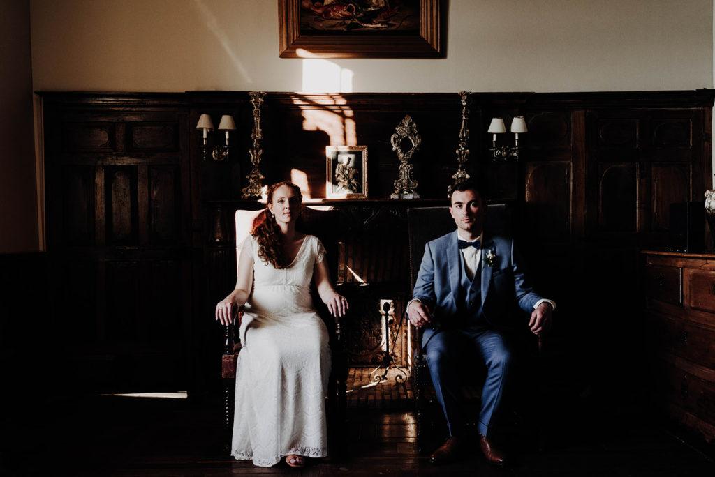 photo couple mariés assis sur trone de chambre médiévale