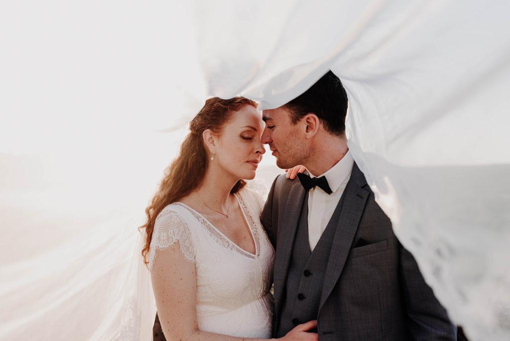 photo de couple avec voile de mariée dans le vent